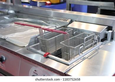 New empty modern professional fryer basket in kitchen restaurant ; Food Industrial background