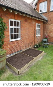 A new empty raised bed in a kitchen garden is filled with soil ready to plant