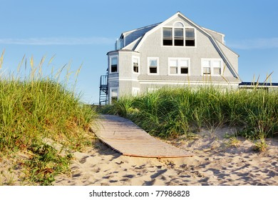 New England beach house by the boardwalk in early morning sun