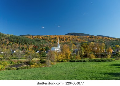 New England Fall with Peak Colors and a Small Village with a Church and Blue Sky