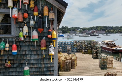 New England Lobster Fishing Dock:  Marker buoys for lobster traps decorate the side of a fishing shack on a wharf in Maine.