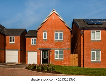 New English red brick build homes in a residential development in central England, UK. Detached traditional houses with black door and garage.
