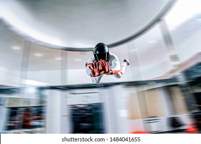 New entertainment. People fly indoor skydiving.  Men learning fly in wind tunnel. Men in white suit and black helmet