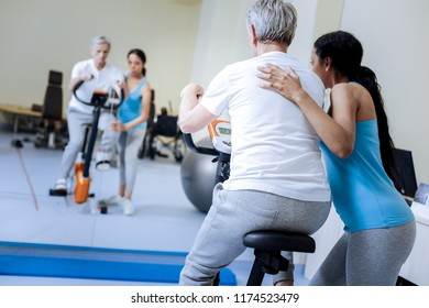 New exercises. Calm attentive enthusiastic medical worker helping her energetic aged patient to recover while showing him new exercises on an exercise bike