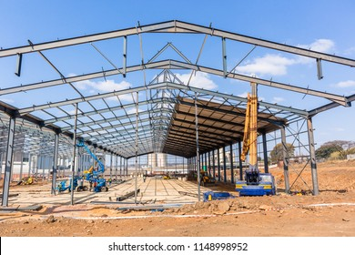 New factory large warehouse construction steel beams frames assembled halfway to completion.