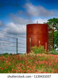New farm barbwire fence, old rusty gas tank and field with beautiful red wild flowers. Texas rural view.