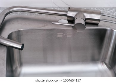 New faucet lying on new kitchen sink ready for installation. Close up