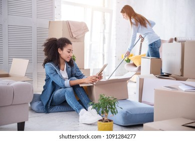 In new flat. Pleasant young girl cleaning the floor with a mop while her roommate sitting on the floor and looking a framed photo during unpacking of belongings