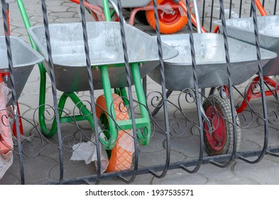 New garden wheelbarrows on one wheel for sale. Farmer's store. A group of new trolley behind a metal fence. Industry trade.