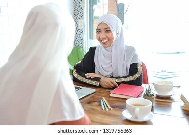 new generation businesswoman muslim people meeting in coffee shop with computer and coffee cup on wood desk