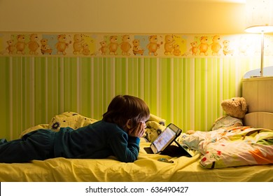 New generation kid using tablet pc at home. Child watching movie on tablet computer in bed. Education school technology internet concept