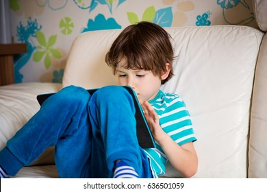 New generation kid using tablet pc at home. Child playing games on tablet computer on a sofa. Education school technology internet concept