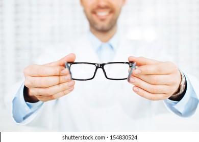 42ab011d2c8e New glasses. Closeup of optician, optometrist giving eyeglasses to try