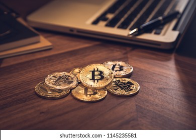 New gold Bitcoins and Litecoins on wooden table. Notebook, book, pen in background with dark room light. Modern business style, concepts for blockchain, cryptocurrency, digital money and investment.