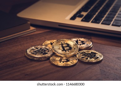 New gold Bitcoins on wooden table. Notebook and book in background with dark room light. Modern business style, concepts for blockchain, cryptocurrency, digital money exchange and investment fund.