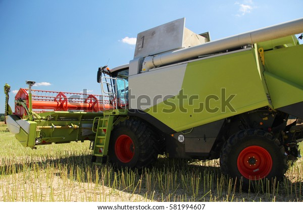 New grain combine harvesting oilseed rape during sunny summer day with blue sky, side perspective, bio agriculture, fertilized field with slurry