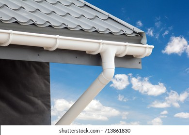 New gray metal tile roof with white rain gutter