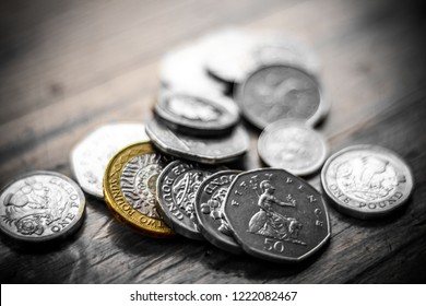 New Great British Pound GBP Coins laying casually on top of black wallet on wooden surface. Wealth, Money, Cash, Change.
