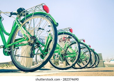 New green bicycles lined up on the road - Detail of wheels at bycicle sharing point - Modern concept of ecological transportation - Bike urban transport