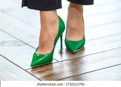 new green shoes on the girl's legs close-up. Shoes - shoes covering the leg no higher than the ankle. Heel stiletto heel on new designer shoes. green elements of female accessories.