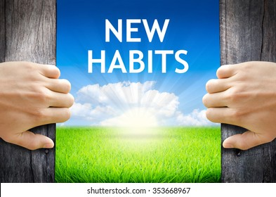 """New Habits. Hand opening an old wooden door and found wording """"New Habits."""" over green field and bright blue Sky Sunrise."""
