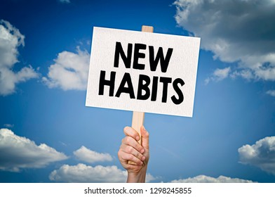New habits message on board in hand with sky background