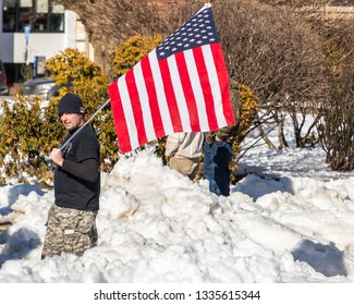 New Hampshire Gun Rights Rally at the Capital House in Concord, NH.  Saturday, March 9, 2019. A man in Black hat and black t-shirt is holding an American flag on his shoulder.