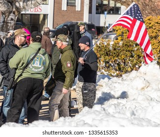 New Hampshire Gun Rights Rally at the Capital House in Concord, NH.  Saturday, March 9, 2019. A man standing front of a group of people is holding an American Flag on his shoulder.