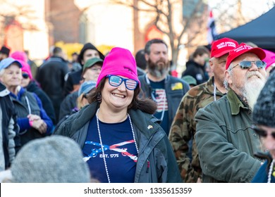 New Hampshire Gun Rights Rally at the Capital House in Concord, NH.  Saturday, March 9, 2019. A lady wearing eye glasses with the American flag if smiling.