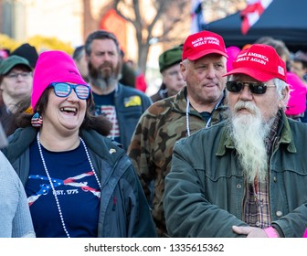 "New Hampshire Gun Rights Rally at the Capital House in Concord, NH.  Saturday, March 9, 2019. Men wearing ""Make America Great Again"" hat are standing by a lady laughing out loud."