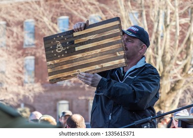 New Hampshire Gun Rights Rally at the Capital House in Concord, NH.  Saturday, March 9, 2019. A man is holding a hand made woodern American flag.
