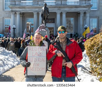 New Hampshire Gun Rights Rally at the Capital House in Concord, NH.  Saturday, March 9, 2019. A man holding a raffle gun and another with a sign are standing at the entrance of the capital house.