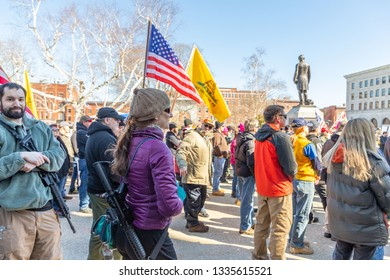New Hampshire Gun Rights Rally at the Capital House in Concord, NH.  Saturday, March 9, 2019. Woman in purple is holding a raflle gun on her shoulder.