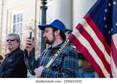 New Hampshire Gun Rights Rally at the Capital House in Concord, NH.  Saturday, March 9, 2019. A man is holding American flag on his shoulder.