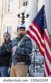 New Hampshire Gun Rights Rally at the Capital House in Concord, NH.  Saturday, March 9, 2019. Holding a flag on his shoulder, a man is recording with his cellphone