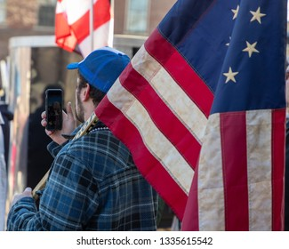 New Hampshire Gun Rights Rally at the Capital House in Concord, NH.  Saturday, March 9, 2019. A man is holding American flag on his shoulder