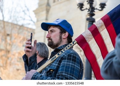 New Hampshire Gun Rights Rally at the Capital House in Concord, NH.  Saturday, March 9, 2019. A man recording a video with his cell phone is holding American flag on his shoulder