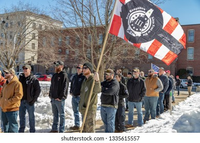 New Hampshire Gun Rights Rally at the Capital House in Concord, NH.  Saturday, March 9, 2019. A man standing front of a line of people is holding a flag.
