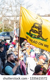 "New Hampshire Gun Rights Rally at the Capital House in Concord, NH.  Saturday, March 9, 2019. A man is raising a yellow flag saying ""don't tread on Me"""