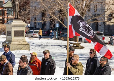 New Hampshire Gun Rights Rally at the Capital House in Concord, NH.  Saturday, March 9, 2019. A man is in a line of people is holding protesters' flag.