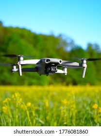 New Hampshire, USA - July 13, 2020: DJI Mavic Air 2 drone hovering above field of yellow flowers on sunny summer day