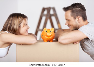 New happy couple looking at the piggybank in a savings concept