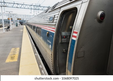 NEW HAVEN, CONN. - MARCH 2018: Passengers board Amtrak train at outdoor station - platform at New Haven, Connecticut. The Vermonter awaits engine change