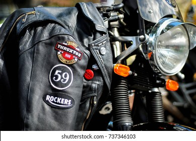 NEW HAVEN, CT, USA - AUGUST 2012: A leather jacket with patches draped over a classic Norton cafe racer motorcycle