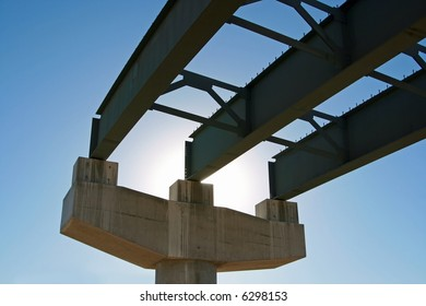 New highway bridge being built - viewed from underneath and looking toward the sun. This portion of the bridge is incomplete and there's no road decking.