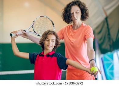 New hobby. Dark-haired kid having a tennis workout with his female coach