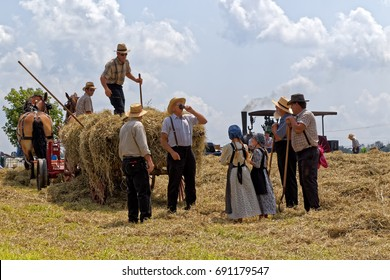NEW HOLLAND, PENNSYLVANIA - August 4, 2017: Two Mennonite girls take water to the hay crew at Big Spring Farm Days. This is an annual event demonstrating traditional threshing and harvesting methods.