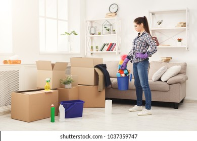 New home cleaning. Young woman tiding up after moving to new appartment. Girl with various detergents, rags and mops in living room full of carton boxes. Household and spring-cleanig concept