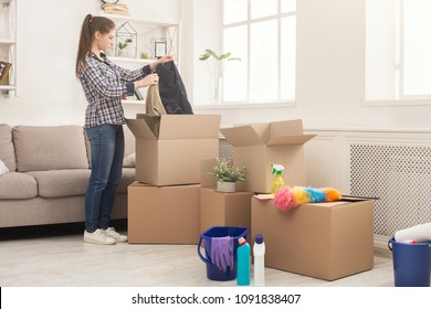New home cleaning. Young woman tidying up and unpacking boxes after moving to new apartment. Girl with various detergents, rags and mops in living room full of carton boxes.