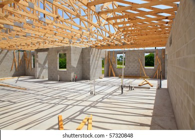 New home Construction of a cement block home with wooden roof trusses.